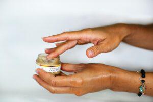 des doigts dans un pot de crème hydratante pour les main
