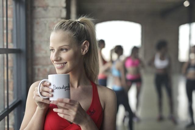 Femme buvant une tisane composée de produits naturels pour éviter les courbatures et crampes durant sa séance de sport.